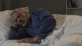Old male lying in his bed and sleeping, recovery time and healthy sleep, night. Stock footage Royalty Free Stock Photos