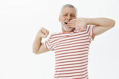 Old male pensioner feeling lazy today. Carefree relaxed handsome senior man with beard and grey hair in striped t-shirt. Stretching and yawning covering opened royalty free stock photos