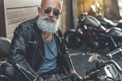 Old male person ready to ride motorbike Royalty Free Stock Image