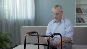 Old male sitting on couch and looking at walking frame standing in front of him. Stock footage stock footage