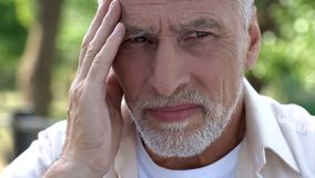 Old male suffering migraine, health problems, brain cancer risk, painkillers stock photography