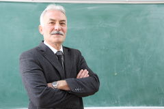 The Old Male Teacher in the classroom. The teacher in the classroom in front of Stock Photo
