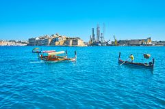The old Maltese boats, Valletta. VALLETTA, MALTA - JUNE 17, 2018: The dghajsa water taxi and luzzu fishing boats in Grand Harbour of Valletta with a view on Stock Image