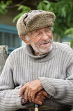 Old man. BYHIV, UKRAINE - JUNE 11 - An unidentified elderly man in winter hat in summer sitting at outdoor in Byhiv on Julne 11, 2013. Poverty is a big problem Royalty Free Stock Photos