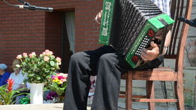 Old man accordion. Wrinkled senior man hands playing with an old accordion outdoor stage on June 08, 2013 in Birzai, Lithuania stock video footage