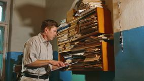 Old man accountant in an old office examines paper reporting the documents. old businessman professional working office. Old man accountant in an old office stock video footage