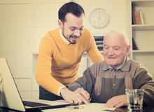 Old man and agent sign lease contract. Elderly men and young agent sign lease contract of apartment at office Stock Photography