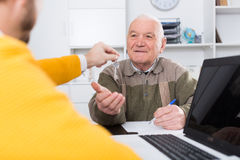 Old man and agent sign lease contract. Old men and agent sign lease contract of apartment in agency royalty free stock images