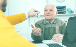 Old man and agent sign lease contract. Pensioner and lease agent sign lease contract of apartment at office and hand over keys royalty free stock photo