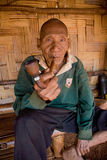 An old man of the Akha ethnic group stay in the shadow of his bamboo house, smoking with a wooden pipe Royalty Free Stock Images