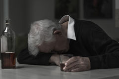 Old man alcoholic. Old retired man alcoholic sleeping on the table stock photos