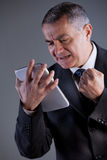 An old man angry with a tablet Royalty Free Stock Images