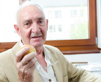 Old man with apple Stock Image