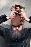 Old man, artist with beard has a hand puppet on his head royalty free stock images