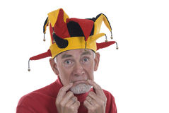 Old man as clown in jester's hat. Old man on a white background, wearing a traditional jester's hat and pulling his mouth down to suggest sadness royalty free stock photography
