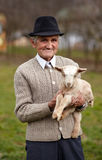 Old man with baby goat Royalty Free Stock Image