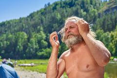 An old man with a bare-chested raised hands straightening his long hair. A man with a beard, long volrs and a naked torso against the backdrop of a mountain stock photos
