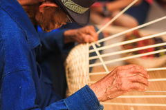 Old man Basket weaving from bamboo. It is made ​​of bamboo strips. Contrary to the General Made objects such as basket-shaped basket. Chiangmai Thailand Stock Photo