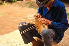 Old man Basket weaving from bamboo Stock Images