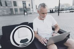 An old man with a beard sits on a sofa in the street. He is holding a laptop in his hands. Near his gyroboard. The old man works Stock Photo