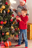 Old man beautifying fir-tree with grandchildren. Grandfather is decorating Christmas tree with children. They are standing and smiling Royalty Free Stock Image