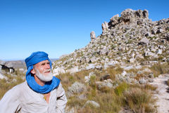 Old man in bedouin clothes looks at mountains Stock Photography