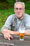 Old man with beer. Old man with glass of beer and cigarette, having a rest at the rustic oak table stock photos