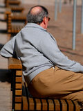 Old man on bench. Man sitting on a bench. He enjoys the sun on his few hair of head Royalty Free Stock Image