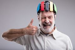 Old man with bicicle head protection. With thumbs up for safety and helmets Royalty Free Stock Photography