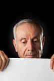 Old man with a blank paper. On black background Royalty Free Stock Photos