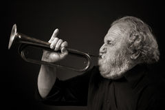 Old man blowing a bugle with gusto. Sepia toned image of a grey bearded musician blowing forcefully on his bugle, which he is holding with an expressively raised Stock Photo