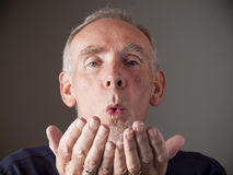 Old man blowing a kiss Royalty Free Stock Images
