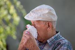 Old man blowing nose in napkin Stock Photo