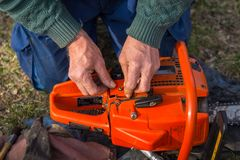 Old man in blue pants repair orange chainsaw placed on the ground with his bare hands.  royalty free stock photography