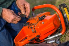 Old man in blue pants repair orange chainsaw placed on the ground with his bare hands.  royalty free stock photo