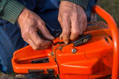 Old man in blue pants repair orange chainsaw placed on the ground with his bare hands.  stock images
