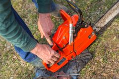 Old man in blue pants starting orange chainsaw.  royalty free stock images