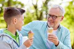 Old man and boy eating ice cream at summer park Royalty Free Stock Photo