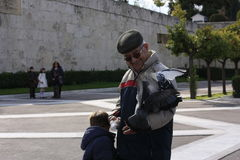 An old man and a boy feeding pigeon in syntagma square,greece Stock Image