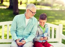 Old man and boy with smartphones at summer park royalty free stock images