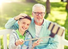 Old man and boy taking selfie by smartphone royalty free stock photos
