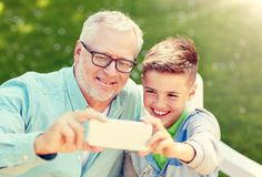 Old man and boy taking selfie by smartphone stock photos