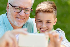 old man and boy taking selfie by smartphone stock photo image 80548136. Black Bedroom Furniture Sets. Home Design Ideas