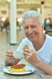 Old man at breakfast Stock Images