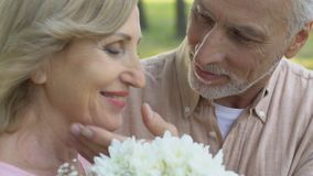 Old man bringing bouquet of flowers to woman and hugging her tenderly with love