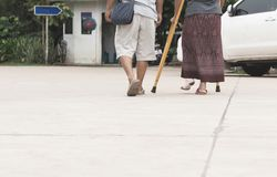 Old man with broken leg old woman walk together royalty free stock image