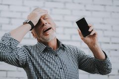Old Man with Broken Mobile Phone Holding Head. stock image