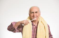 Old man brushing his teeth stock photo