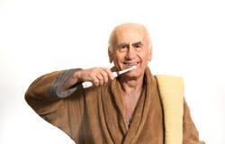Old man brushing his teeth stock images