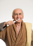 Old man brushing his teeth Stock Images